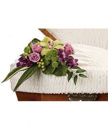 Floral casket insert of one cymbidium orchid, lavender roses, purple alstroemeria and more.