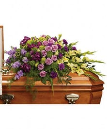 Casket spray of green hydrangea, lavender roses, purple alstroemeria and more.