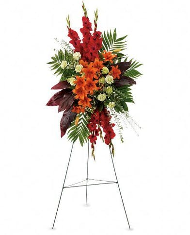 Tropical sympathy spray of red and orange flowers with greenery.