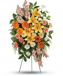 Sympathy spray of lilies and gerbera daisies in shades of peach and orange.