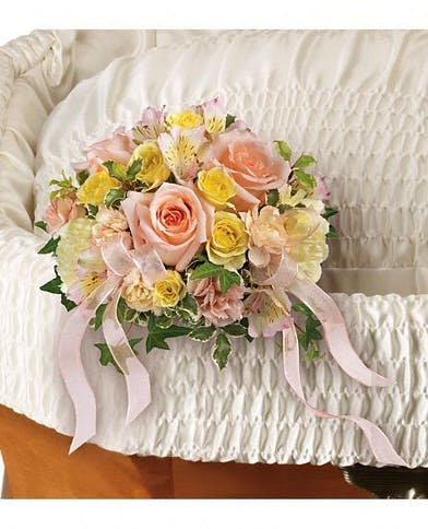 Nosegay of peach roses, yellow spray roses, pink alstroemeria, yellow carnations, and more.