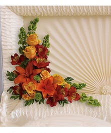 Casket insert of orange roses, spray roses, lilies and more.
