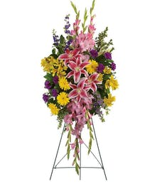 Sympathy spray with pink lilies, yellow gerberas and purple larkspur.