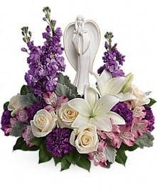 Roses, lilies and alstroemeria flowers surrounding an angel sculpture keepsake.