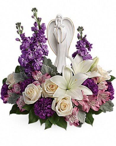 Roses, lilies and alstroemeria flowers surrounding an angel sculpture keepsake.