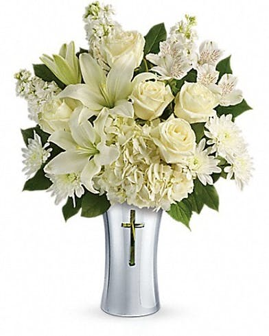 White hydrangea and lilies in a ceramic vase with a cross cut-out.
