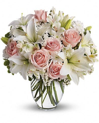 Pink roses and white lilies in a clear glass vase.