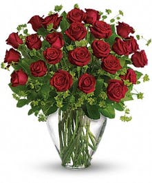 Two Dozen red roses with greenery in a clear glass vase.