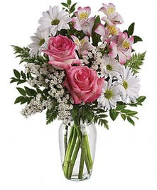 White daisies, pink roses and other assorted flowers in a clear glass vase.