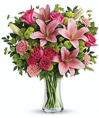 Pink lilies, red roses, pink carnations & more in a clear glass vase.