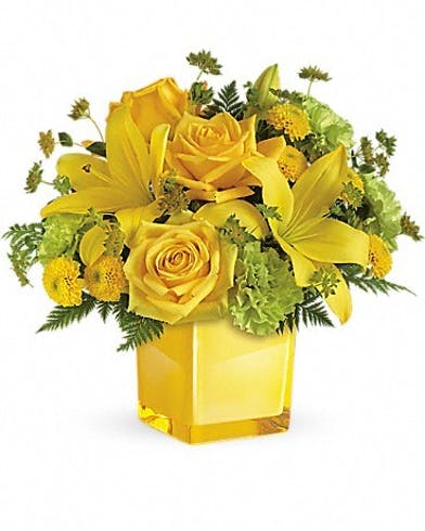 Yellow roses, lilies and more flowers in a yellow cube vase.