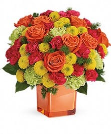 Orange roses, green carnations, pink mini carnations, and yellow button spray chrysanthemums with greenery in an orange cube vase.