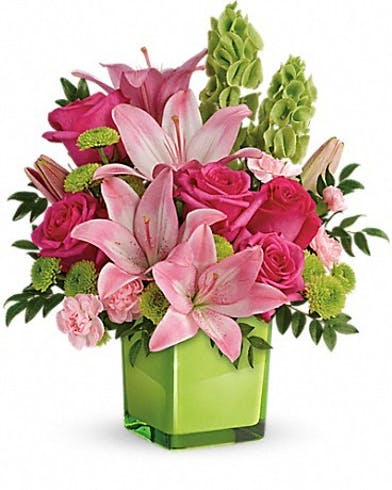 Pink and green flowers in a lime green cube vase.