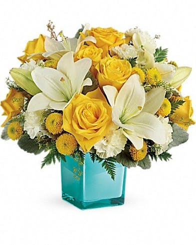Yellow and white flowers in a teal glass cube vase.