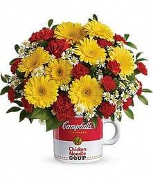 Yellow gerbera daisies and red carnations presented in a Campbell's Soup mug.