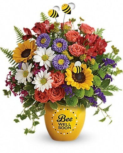 Red, puple, yellow and white flowers in a yellow vase that says