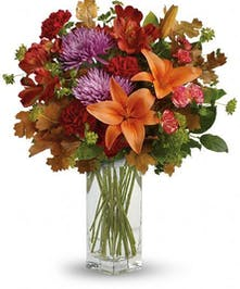 Asiatic lilies, alstroemeria, carnations, chrysanthemums and more in a clear glass vase.