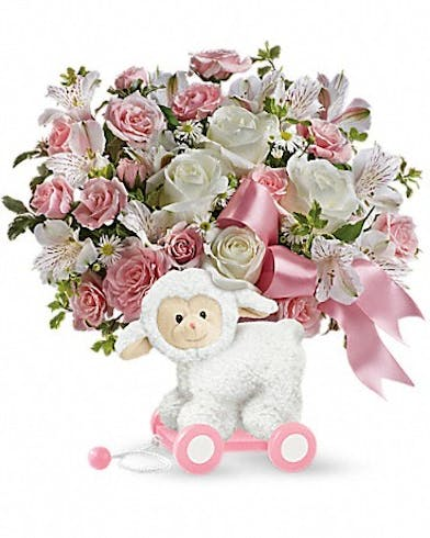 Lamb container filled with pink and white flowers.