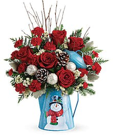 Metal kettle with snowman decoration filled with red roses, pine cones and winter greenery