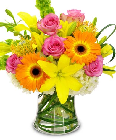 Yellow, pink and orange flowers in a glass vase.