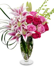 Pink lilies and roses with white orchids in a clear glass vase.