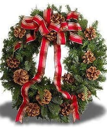 Holiday evergreen wreath with pinecones and festive red ribbon.