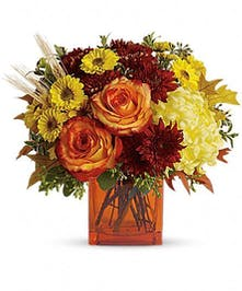 Orange cube vase filled with orange roses and other fall flowers.