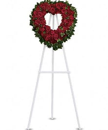 Heart-shaped arrangement of red roses presented on an easel.