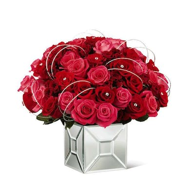 Red roses, hot pink roses and spray roses with rhinestone accents presented in a mirror cube vase.
