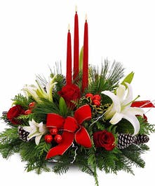 Christmas centerpiece of white lilies, red roses, frosted pinecones, mini ornaments, a red bow and red taper candles.