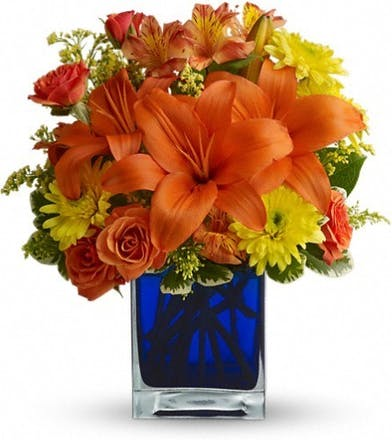 Orange, red and yellow flowers in a blue glass cube vase.