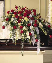 Casket spray of red and white blooms.