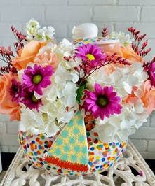 Coton Colors Happy Everything container filled with bright flowers.