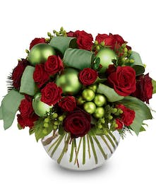 Glass bubble bowl vase filled with red roses and green ornament decorations