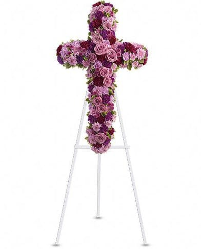 Floral cross made of lavender and purple flowers.