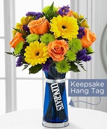 Yellow, orange and purple flowers in a blue glass vase with a Congratulations hang tag.