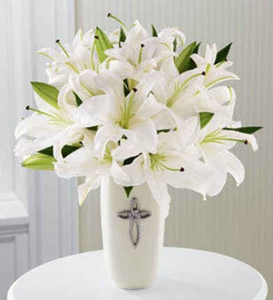 White lilies in a white ceramic planter with cross on the front.