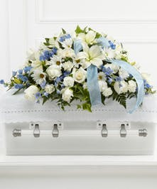 Casket spray of white roses, daisies, and more with blue delphinium and blue ribbon.