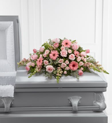 Casket spray of pink roses, gerbera daisies, spray roses, tulips and snapdragons with greenery.