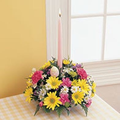 Round flower arrangement featuring taper candle and an Easter egg, yellow daisies, monte casino & pink carnations.