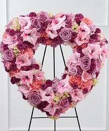 Heart-shaped sympathy wreath of pink flowers presented on an easel.