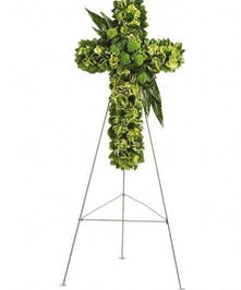 Floral cross made of green flowers and accents.