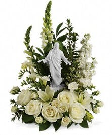 Keepsake Jesus sculpture surrounded by white flowers and greenery.