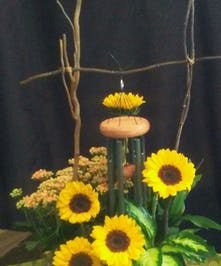 Ceramic container, wind chime and fresh cut sunflowers.