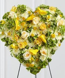 Sympathy heart arrangement of yellow blooms presented on an easel.