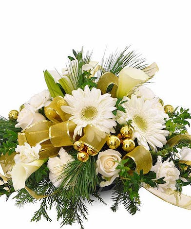 Holiday centerpiece of white flowres and gold ribbon with winter greenery