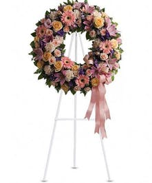 Pastel sympathy wreath accented with pink ribbon.