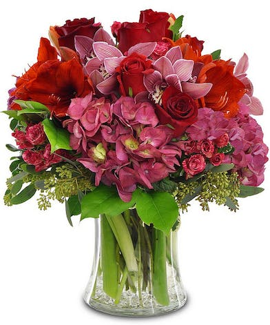 Holiday bouquet of amaryllis, cymbidium orchids, roses, and hydrangea in a clear glass vase.