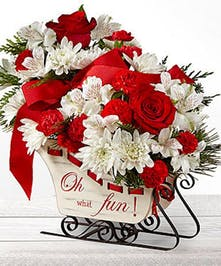 Sleigh arrangement of red and white flowers accented with red ribbon