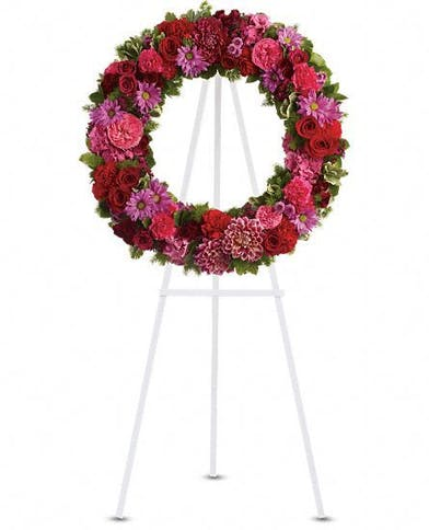 Jewel-toned flower wreath presented on an easel.